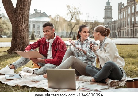 Best friends. Positive delighted brunette girl keeping smile on her face while looking at her friend #1346890994