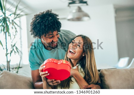 Man giving a surprise gift to woman at home #1346901260