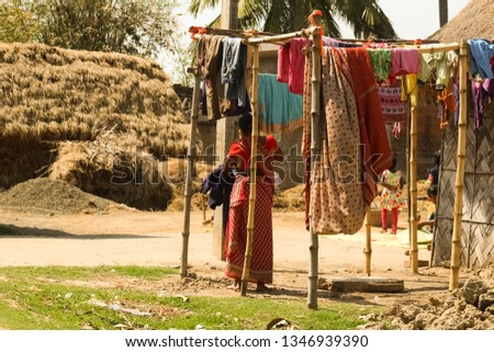 An Indian women drying their wets cloths on a bright sunny day. Colorful clothes hanging on the bamboo/