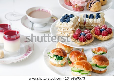 Afternoon tea with mini brioche canapes and selection of sweets Royalty-Free Stock Photo #1346969573