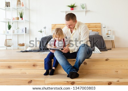 Father and son with tablet at home. Happy father using tablet with his little blond hair son. #1347003803