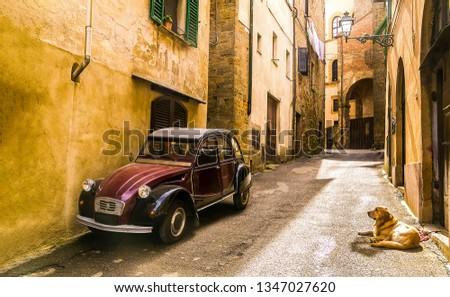 Retro car with dog at narrow street. Dog lying at retro car on narrow street. Retro car and dog on street scene. Ancient narrow street retro car and lying dog #1347027620