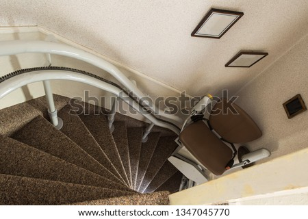 Mechanical chair lift taking disabled or aged people up and down stairs Senior, Stairlift for disabled in a home #1347045770