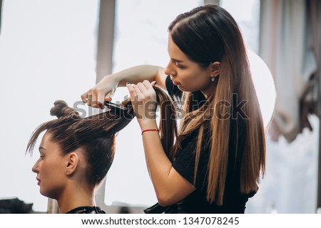Master hairdresser makes hair style girl with hairdryer and hair care products Royalty-Free Stock Photo #1347078245
