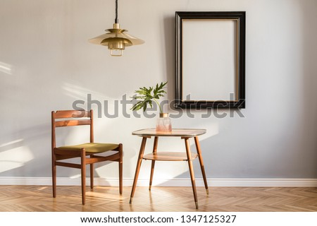 Sunny and design retro interior with design chair, gold lamp, small table with  tropical leaf. Black mock up frame on the grey background wall. Minimalistic concept of sitting room. Real photo.
