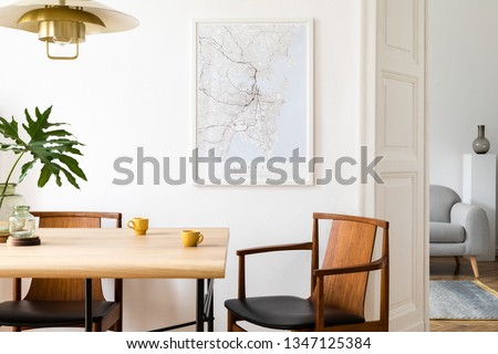 Stylish and eclectic dining room interior with mock up poster map, sharing table design chairs, gold pedant lamp and elegant sofa in second space. White walls, wooden parquet. Tropical leafs in vase. #1347125384