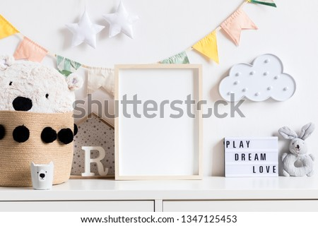 Stylish and modern scandinavian newborn baby interior with mock up photo or poster frame on the white shelf. Toys, teddy bear, plush rabbit and hanging cotton flags, cloud and stars. Cozy decor. Royalty-Free Stock Photo #1347125453