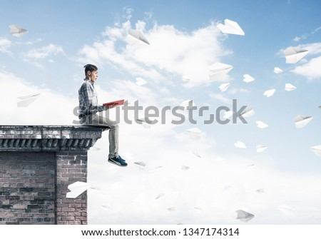 Young man in casual sitting on building top with red book in hands #1347174314