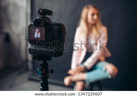 close up photo, focus on a working digital camera at the studio, blurred background