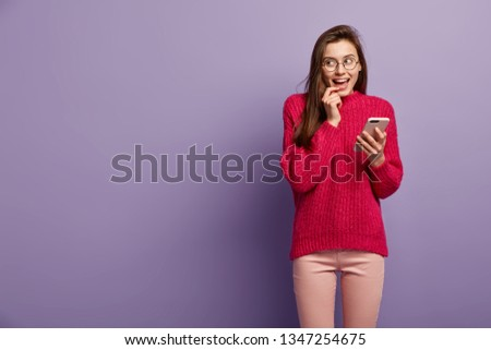 Dreamy cheerful lovely woman uses smart phone for taking pictures, thinks over received notification, looks gladfully aside, surfs internet, wears long knitted sweater, isolated over purple wall #1347254675