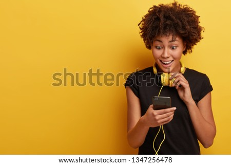 Beautiful dark skinned lady recieves funny video from friend, looks surprisingly at cell phone, listens audio with headphones, dressed in black clothes, listens music, isolated on yellow studio wall #1347256478