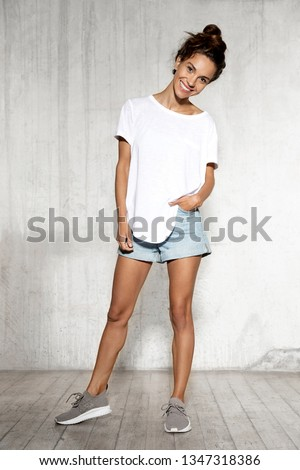 Full length portrait of bronze skinned tanned girl wearing white shirt with copy space blue jeans shorts and grey shoes. Cute cheerful woman holding hands in pockets. Casual style and fashion concept #1347318386