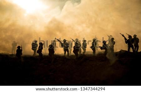 Battle scene. Military silhouettes fighting scene on war fog sky background. World War Soldiers Silhouettes Below Cloudy Skyline At sunset. Artwork Decoration. Selective focus #1347344294