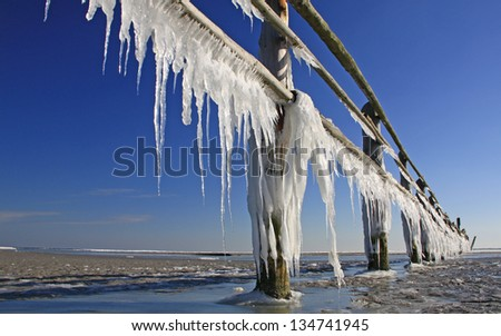 Icicles on a wooden fence at the Baltic Sea, Western Pomerania Lagoon Area National Park, Mecklenburg-Western Pomerania, Germany Royalty-Free Stock Photo #134741945