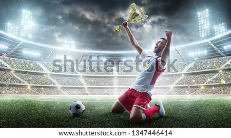 Professional soccer player celebrates winning the open stadium. Soccer player holds a trophy. Medal on the neck. The winner of the soccer cup #1347446414
