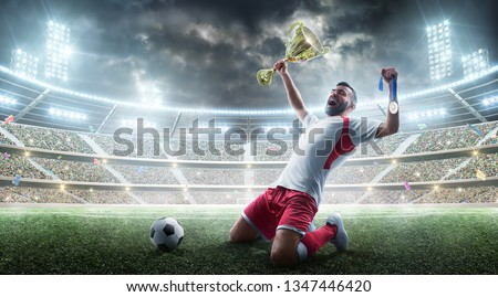 Soccer. Professional soccer player celebrates winning of soccer match the open stadium. Soccer player holds a cup and a medal in his hands. #1347446420