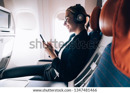 Cheerful female passenger in headphones for noise cancellation watching online movie during intercontinental flight in cabin of aircraft,happy young woman using wifi connection on board, playing games #1347481466