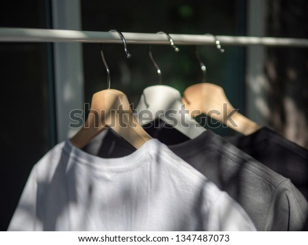 Black, grey and white t-shirts on hangers, close up view  #1347487073