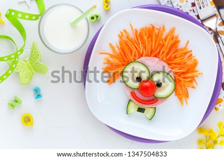 Fun food for kids - cute smiling clown face on ham sandwich decorated with fresh cucumber, carrots and tomatoes for a healthy lunch for children. Creative cooking idea #1347504833