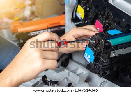 Business man or technician is checking and changing the printer equipment cartridges tone of laser jet multi function printer in the office. Close-up shot of CMYK ink cartridges for laser printer. #1347514346