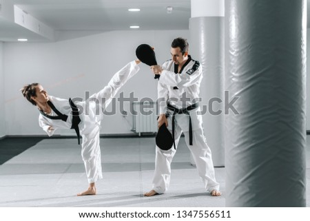 Caucasian handicapped highly motivated girl practicing taekwondo with her training. Girl kicking kick target. #1347556511