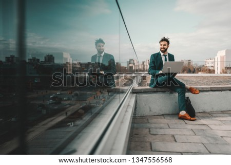Young smiling cheerful Caucasian bearded businessman in formal wear using laptop while sitting on rooftop. At first they will ask you why you are doing it, later they will ask you how you did it. #1347556568