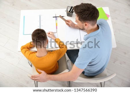 Dad helping his son with homework in room, above view #1347566390