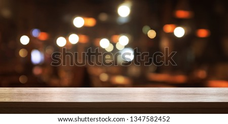 Empty wooden table top with blur coffee shop or restaurant interior background, Panoramic banner. Abstract background can be used for display or montage your products.  #1347582452