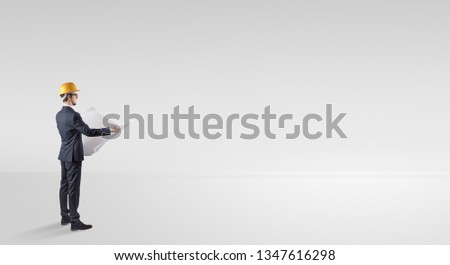 Young architect with construction helmet standing in an empty space and holding a plan #1347616298