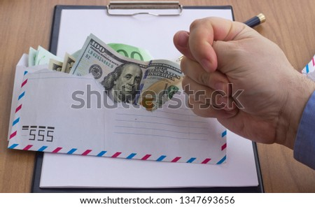 Corruption and bribery . Money in an envelope for signing the document. financial and tax crimes, currency for bribe takers. concept of the celebration International Anti-Corruption Day. copy space. #1347693656