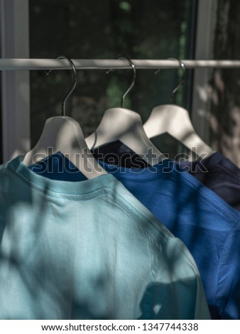 Blue t-shirts on hangers, close up view  #1347744338