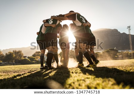 Rugby team standing in a huddle and rubbing their feet on ground. Rugby team celebrating victory. #1347745718