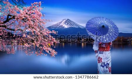 Asian woman wearing japanese traditional kimono at Fuji mountain and cherry blossom, Kawaguchiko lake in Japan. #1347786662