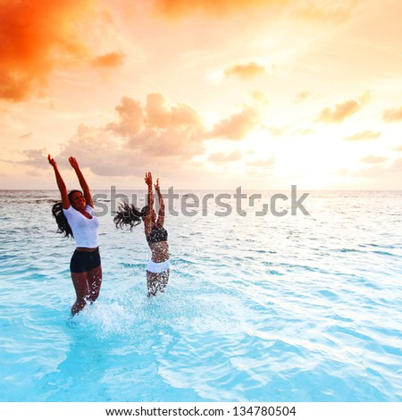 Two happy wimen playing in water on sunset #134780504