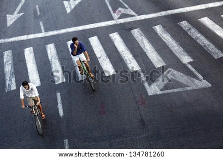 TEL AVIV - OCT 8: Unidentified men riding on bicycles at the empty Maariv intersection in Tel-Aviv on October 8 2011 in Tel Aviv, Israel. #134781260