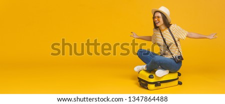 Horizontal banner of young tourist girl sitting on suitcase, pretending flying on a plane, isolated on yellow background with copy space. Dreams about traveling concept #1347864488