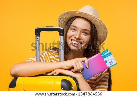 Travel concept. Young happy female student traveller holding passport with flight tickets and suitcase, isolated on yellow background #1347864536