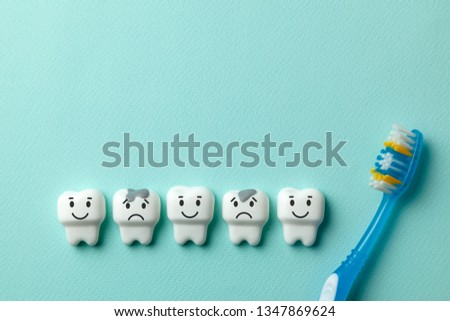 Healthy white teeth are smiling and tooth with caries is sad on green mint background and Toothbrush #1347869624