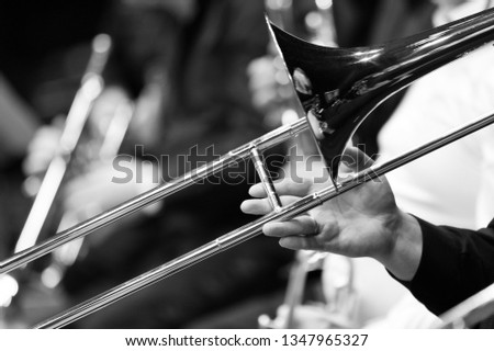 Hand of man playing the trombone in black and white #1347965327