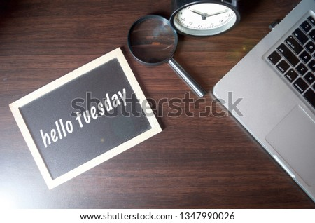 "Blackboard writing ""hello tuesday"" on wooden desk background with laptop, magnifying and alarm clock. Conceptual image. Selective focus."