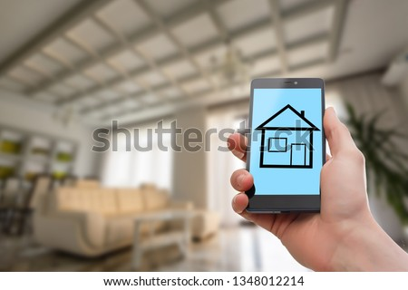 Hand holding mobile phone with house sale offer #1348012214