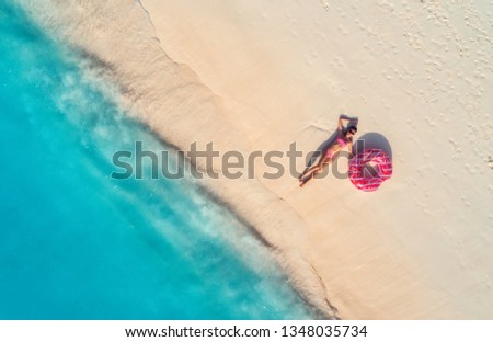Aerial view of the beautiful young lying woman with pink donut swim ring on the white sandy beach near sea with waves at sunset. Summer holiday. Top view of slim girl, clear azure water. Indian Ocean #1348035734