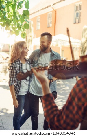 Young loving couple enjoying street musician with a violin #1348054946