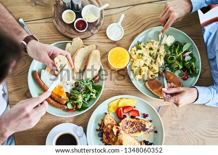 Overhead picture of couple eating tasty breakfast at restaurant. #1348060352