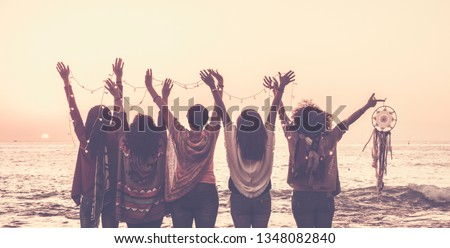 Vintage tones pictures of five women friends viewed from rear giving up hands for happiness in front ona sunset on the ocean and holding lights and a dreamcatcher for spiritual concept