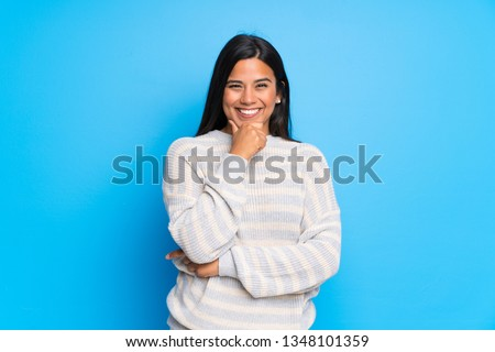 Young Colombian girl with sweater smiling and looking to the front with confident face #1348101359
