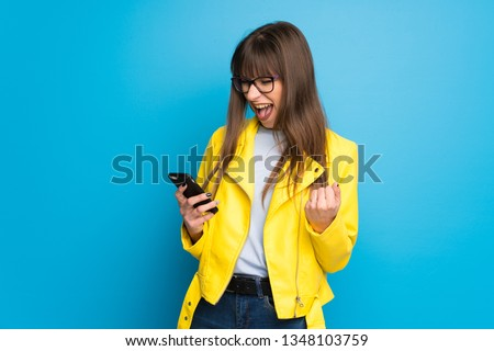 Young woman with yellow jacket on blue background celebrating a victory with a mobile #1348103759