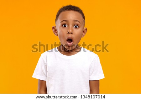 Surprise, excitement and fascination concept. Funny bug eyed African little boy opening his mouth widely, shocked with astonishing unexpected news, having amazed look, showing full disbelief Royalty-Free Stock Photo #1348107014