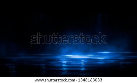 Dark empty scene, blue neon searchlight light, wet asphalt, smoke, night view, rays.