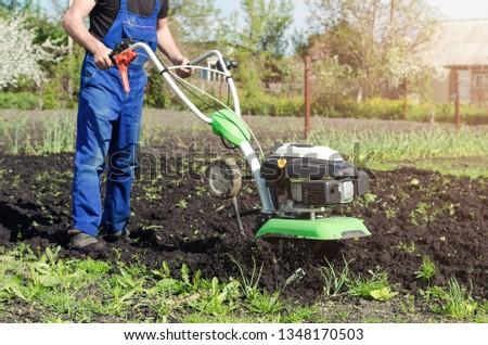 Man working in the spring garden with tiller machine. #1348170503